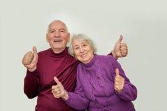 Старшие пары показывая одобренные большие пальцы руки вверх на белой предпосылке стоковое фото rf
