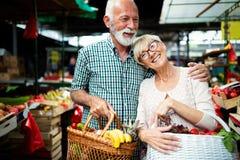 Старшие пары покупок с корзиной на рынке диетпитание здоровое стоковые изображения rf
