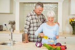 Старшие пары подготавливая vegetable салат стоковое изображение
