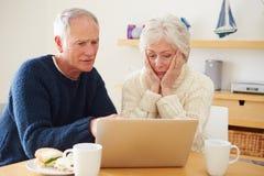 Старшие пары при финансовые проблемы смотря компьтер-книжку Стоковая Фотография RF