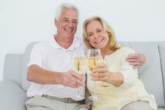 Старшие пары провозглашать каннелюры шампанского дома Стоковое Изображение