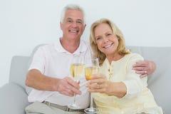 Старшие пары провозглашать каннелюры шампанского дома Стоковая Фотография