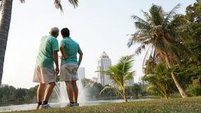 Старшие пары работают в городском парке на рано утром стоковое изображение rf