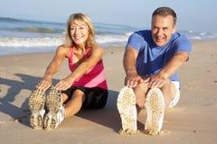 Старшие пары работая на пляже Стоковое Фото