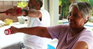 Старшие пары работая с гантелью дома акции видеоматериалы