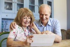 Старшие пары сидят дома используя таблетку цифров совместно стоковые изображения rf