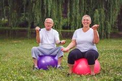 Старшие пары сидящ на шариках фитнеса с гантелями в парке Стоковые Изображения RF