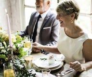 Старшие пары сидя жизнерадостное совместно торжество годовщины Стоковое Изображение RF