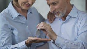 Старшие пары сидя на кресле, человеке задерживая ключи дома, приобретение недвижимости акции видеоматериалы
