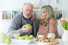Старшие пары сидя на кухонном столе стоковое изображение rf