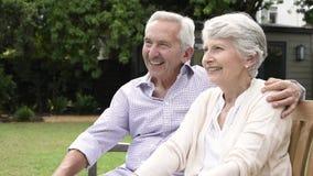 Старшие пары сидя на стенде и говорить акции видеоматериалы