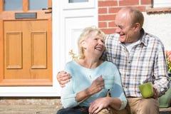 Старшие пары сидя вне дома с чашкой кофе Стоковая Фотография RF