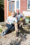 Старшие пары сидя вне дома с чашкой кофе Стоковая Фотография