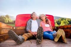 Старшие пары сидя внутри подпирают красного грузового пикапа Стоковая Фотография RF