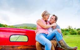 Старшие пары сидя внутри подпирают красного грузового пикапа Стоковая Фотография