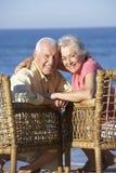 Старшие пары сидя в стульях ослабляя на пляже Стоковые Фотографии RF