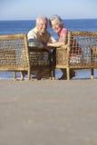 Старшие пары сидя в стульях ослабляя на пляже Стоковая Фотография