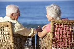 Старшие пары сидя в стульях ослабляя на пляже Стоковое Изображение RF