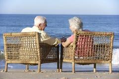 Старшие пары сидя в стульях ослабляя на пляже Стоковое Изображение