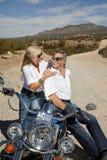 Старшие пары сидя на мотоцикле и усмехаясь на одине другого Стоковая Фотография