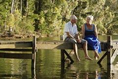 Старшие пары сидя на пристани на озере стоковые изображения