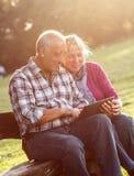 Старшие пары сидя на скамейке в парке смотря таблетку Стоковое Изображение RF