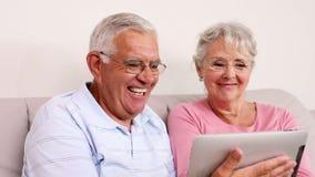 Старшие пары сидя на софе используя ПК таблетки сток-видео