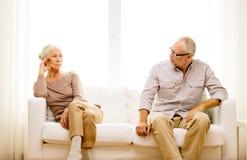 Старшие пары сидя на софе дома стоковое фото