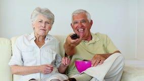 Старшие пары сидя на софе смотря ТВ сток-видео