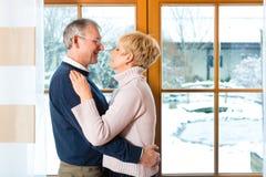 Старшие пары смотря или обнимать окна Стоковое Изображение RF
