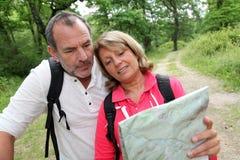 Старшие пары смотря пеший туризм карты Стоковая Фотография