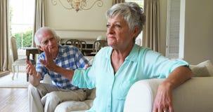 Старшие пары споря друг с другом в живущей комнате сток-видео