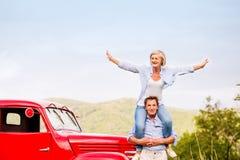 Старшие пары стоя на красном винтажном автомобиле Стоковая Фотография