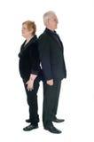 Старшие пары стоя спина к спине стоковая фотография