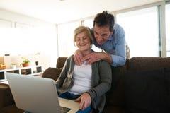 Старшие пары с компьтер-книжкой на кресле в живущей комнате Стоковые Фото