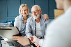 Старшие пары с консультантом на офисе стоковое фото