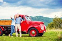 Старшие пары с красным автомобилем Стоковое Изображение RF