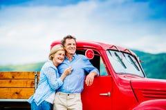 Старшие пары с красным автомобилем Стоковые Изображения
