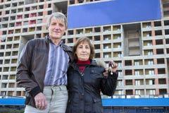 Старшие пары с ключом дома в руке против голубого пустого знамени на здании Стоковое Фото