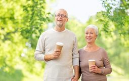 Старшие пары с предпосылкой кофейных чашек естественной стоковое фото
