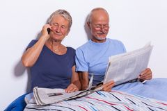 Старшие пары с таблеткой и газетой в кровати Стоковые Фото