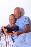 Старшие пары с таблеткой и газетой в кровати Стоковые Изображения