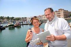 Старшие пары туристов посещая городок морем и используя таблетку стоковое фото rf