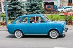 Старшие пары управляя голубым Фиат 850 на местной выставке автомобиля ветерана стоковая фотография rf