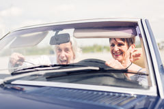 Старшие пары управляя обратимым классическим автомобилем Стоковая Фотография RF