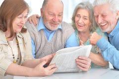 Старшие пары читая газету Стоковые Фотографии RF