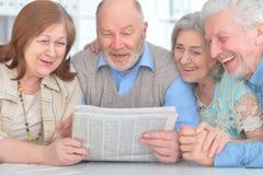 Старшие пары читая газету Стоковое Изображение