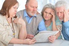 Старшие пары читая газету Стоковое Фото