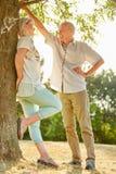 Старшие пары flirting под деревом Стоковое фото RF