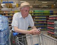 Старшие покупки в супермаркете стоковая фотография